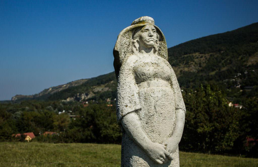 Pomnik Matki Boskiej. W tle - wzgórze z ruinami